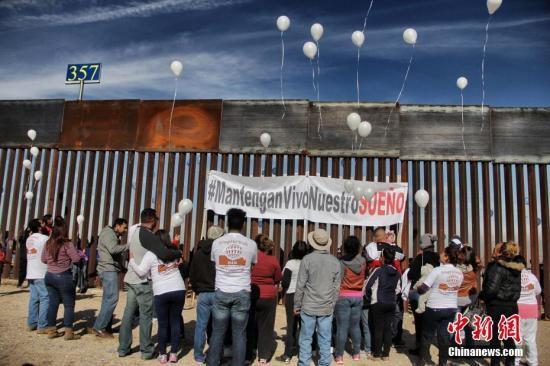 """据美国媒体报道,参与《梦想法案》的80万年轻无证移民,他们中的一些人星期天来到美墨边境 参加""""让梦想继续""""活动,与边境另一侧的家人隔着围栏团聚。活动的发起方是""""边境梦想者联盟(Border Dreamers Alliance)""""。"""