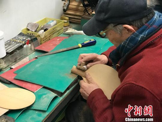 图为曹立熹正在演示乒乓球拍的制作过程。 岳依桐 摄
