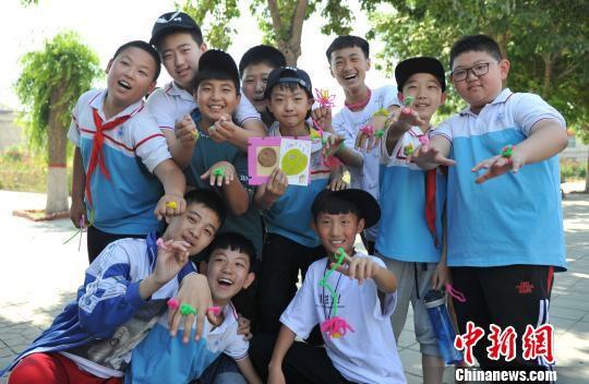 中关村第三小学雄安校区学生展示北京市非物质文化遗产――北京绒花。 韩冰 摄