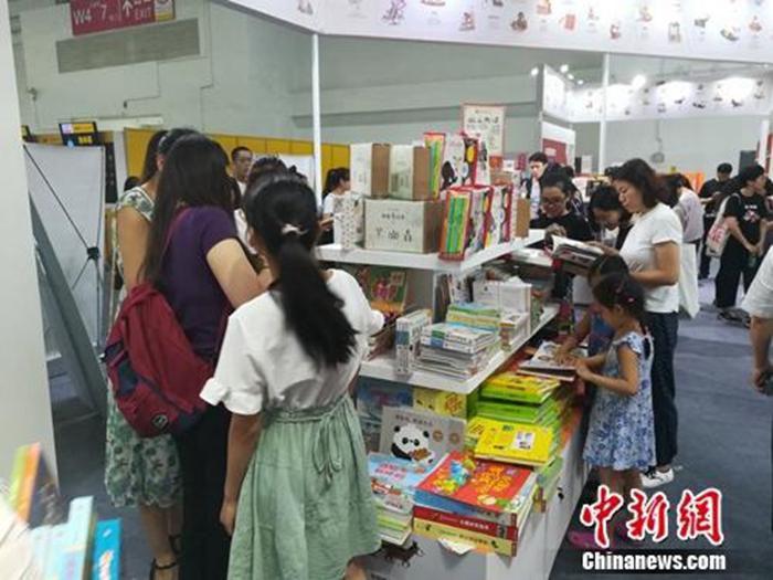 资料图:图博会上,童书展台吸引很多参观者。上官云 摄