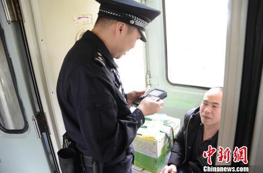 在车上,赵云鹏认真地查验旅客身份证和车票。 孟祥龙 摄