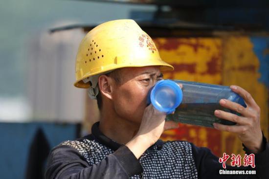 烈日下工人在喝水。肖晨威 摄