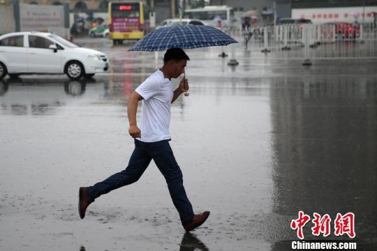 图为民众雨中追赶公交车。 张远 摄