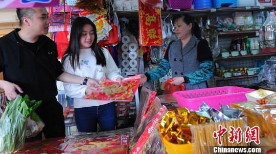 赵云鹏和妻子一起到市场买对联。 蒋雪林 摄