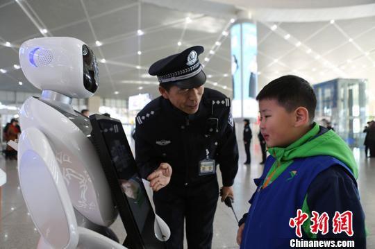 图为民警为小朋友讲解机器人如何使用。 梅森 摄