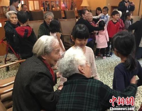 资料图:北京一家养老机构内,老人们与幼儿园小朋友一起做游戏。 杜燕 摄
