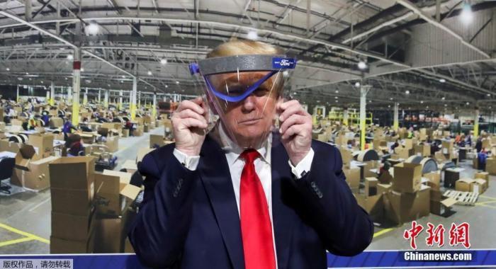 图为美国总统特朗普手举防护面具。