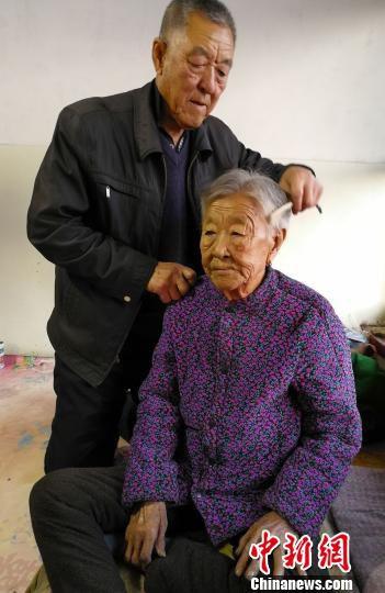 除夕当天,74岁的吴满峥为93岁的母亲张桂兰洗脸梳头,准备迎接新年。 杨杰英 摄