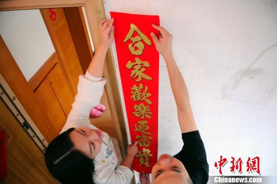 赵云鹏和妻子一起贴对联。 蒋雪林 摄