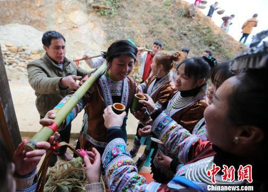 新娘家送亲队伍在新郎家门口被敬进门酒。 石峰 摄