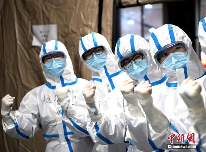 """资料图:武汉""""方舱医院""""医护人员在进入病区前加油鼓劲。 安源 摄"""