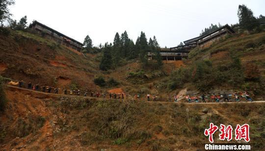 送亲队伍带着新娘一起列队步行往新郎吴彦宣的家。 石峰 摄
