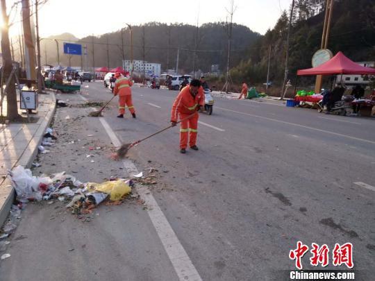环卫工人清扫集市上的垃圾 遂昌宣传部提供