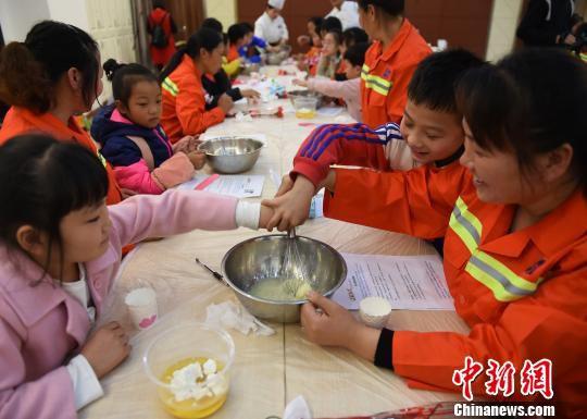 图为环卫工与孩子一起做蛋糕庆祝三八妇女节。 周毅 摄