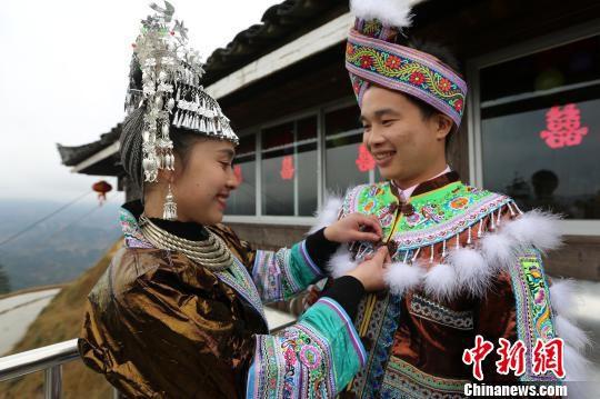 新娘韦英给新郎吴彦宣穿上苗族新郎盛装。 石峰 摄