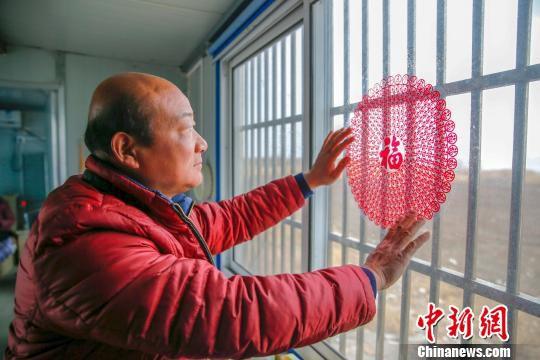 图为大年三十,朱亚华贴窗花迎新春。 汤德宏 摄