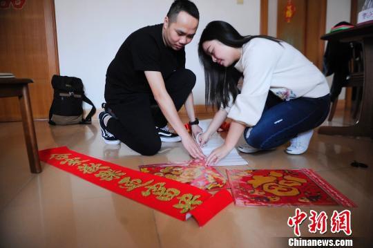 赵云鹏和妻子贴对联。 蒋雪林 摄