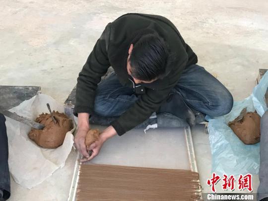 图为工人席地而坐,制作藏香。 王立林 摄