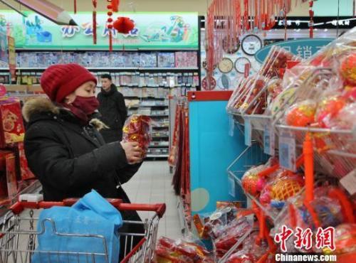 资料图:市民在商超挑选新春装饰。 赵晓 摄