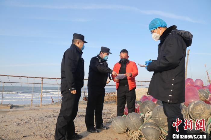 """张凯来到偏远的渔民家送""""防疫温馨提示""""。 曲寓直 摄"""