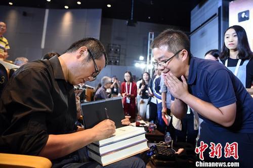 """资料图:2018年9月18日,世界公众科学素质促进大会的""""科幻在促进公众科学素质中的先锋价值""""专题讨论在北京中国科技馆举行。图为中国著名科幻作家刘慈欣(左)为""""粉丝""""签名。<a target='_blank' href='http://www.chinanews.com/'>中新社</a>记者 侯宇 摄"""