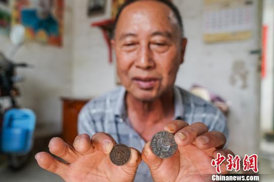 图为龙英禄展示的铜币。 陈冠言 摄