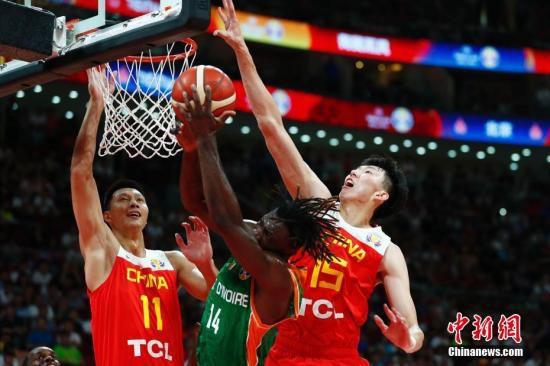 资料图:8月31日,中国球员周琦(右)在比赛中封盖。当日,在北京进行的2019年国际篮联篮球世界杯A组小组赛中,中国队以70:55战胜科特迪瓦队。 <a target='_blank' href='http://www.chinanews.com/'>中新社</a>记者 富田 摄