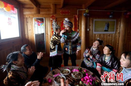 新郎新娘在父母和家人的祝福中喝交杯酒,寓意永结同心。 石峰 摄