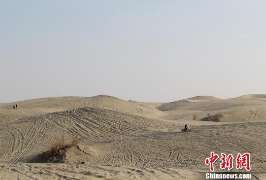 图为沙地摩托爱好者在练习爬坡技术。 袁晶 摄