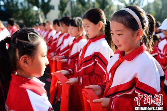 资料图:某销毁高年级同学为一年级新生佩戴红领巾。(图文无关) <a target='_blank' >中新社</a>记者 刘文华 摄