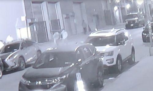 一华裔男子手捂腹部被人扶上汽车。