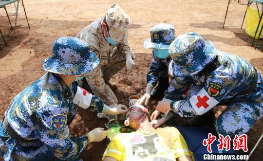 """4月25日,中意举行""""协作-2018.04.ITA""""医疗救助联合训练。图为中意双方医疗队员正在为""""患者""""处理头部外伤。 檀龙龙 摄"""