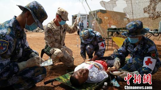 """4月25日,中意举行""""协作-2018.04.ITA""""医疗救助联合训练。图为中意双方救援人员在重伤区处理腹部外伤。 檀龙龙 摄"""