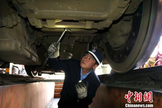 图为陈吕检查机车电机悬挂装置。 李兆根 摄