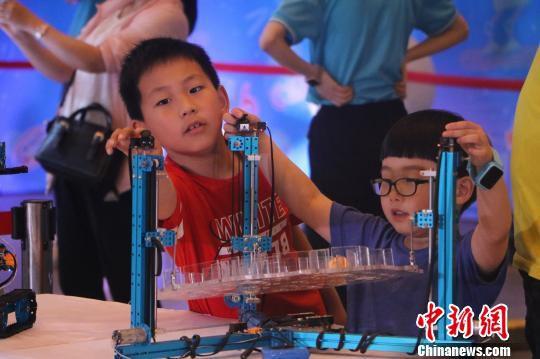 孩子们对机器人爱不释手 赵强 摄