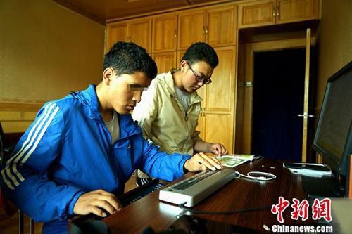 热爱诗歌的次仁是西藏日喀则萨迦县人,他是今年西藏高考唯一一位盲人考生。6月25日,成绩公布,次仁高考总分为422分。这比西藏官方公布的少数民族文史类重点本科录取分数线375分,高出了47分。图为6月29日,次仁(左)和好友普扎西进行盲文翻译。<a target='_blank' href='http://www.chinanews.com/'>中新社</a>记者 江飞波 摄