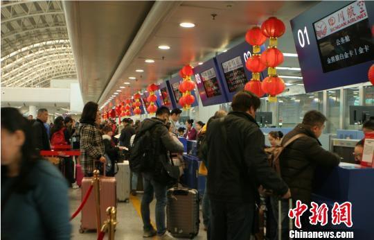 图为旅客等待托运行李。 吕俊明 摄