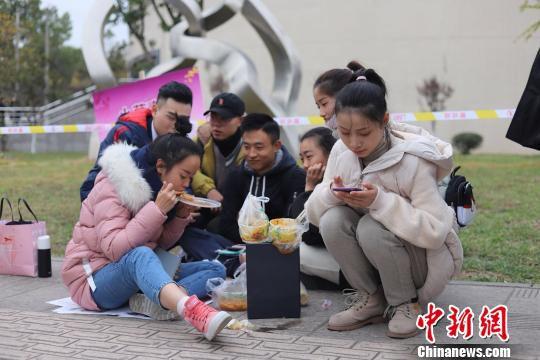 等候考试的学生坐在地上吃饭。 钟欣 摄