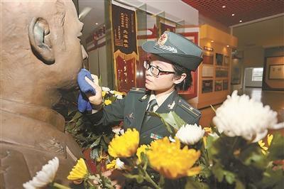 陈勤深情擦拭军史馆里哥哥的铜像。