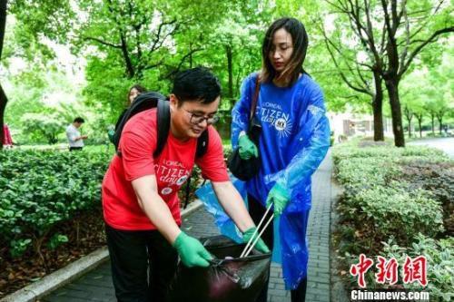 """资料图: 青年志愿者们参加""""环保跑拾活动"""",化身""""行走的垃圾桶"""",身体力行宣传垃圾分类知识。 申海 摄"""