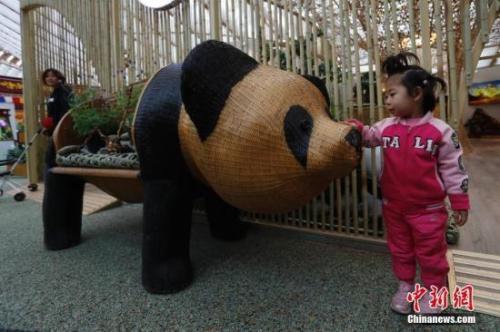 资料图:4月29日,2019年中国北京世界园艺博览会(简称北京世园会)开园,正式对公众开放。图为一名小朋友在中国馆内与熊猫景观合影留念。<a target='_blank' href='http://www.chinanews.com/'>中新社</a>记者 韩海丹 摄
