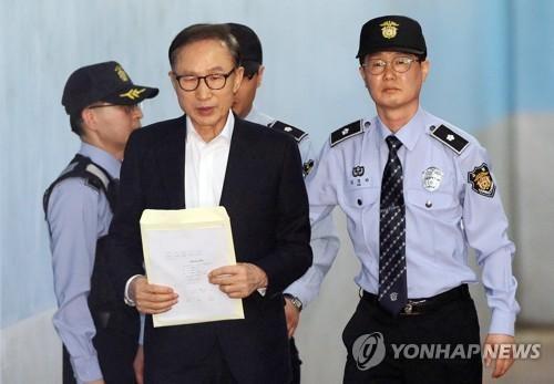 5月23日下午,在首尔中央地方法院,李明博走向法庭。(图片来源:韩联社)