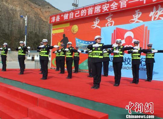 图为甘肃漳县交警为当地学生表演交通指挥手势操,使孩子在听、看、学的过程中对交通安全知识有了进一步的认识。 方爱民 摄