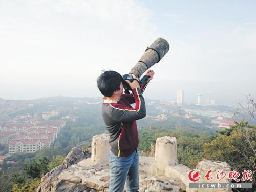攀登到山顶,肖辉跃在拍摄迁徙的候鸟