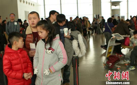 图为旅客排队通过安检。 吕俊明 摄