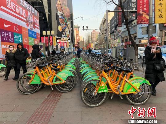 由于来还车的人很多,站点旁经常停满不能放回锁桩的自行车。忙碌的自行车整理工作,梁军已经做了六年。 李庭耀 摄