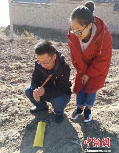 """43岁的吴忠带着女儿吴小菲在毛皂镇东北方位的田间""""迎喜神""""。 杨杰英 摄"""