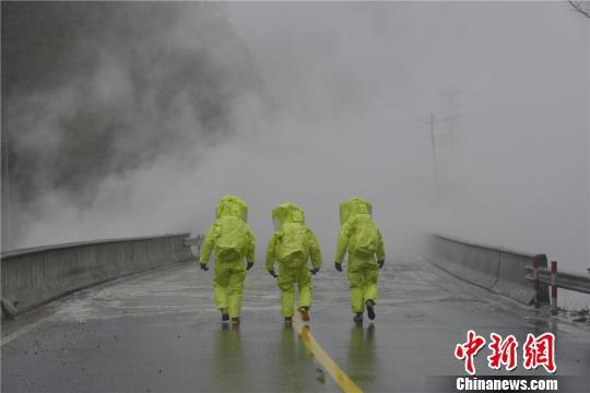 图为:消防员穿上防化服对事故车辆进行关阀堵漏处理。 宋雄伟 摄