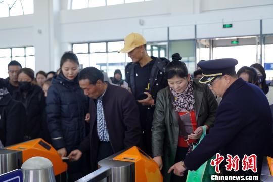 11月2日,青海西宁火车站乘客刷身份证进站乘车。图为西宁站工作人员指导旅客通过身份证识别区读取电子客票检票乘车。 姚雪皎 摄