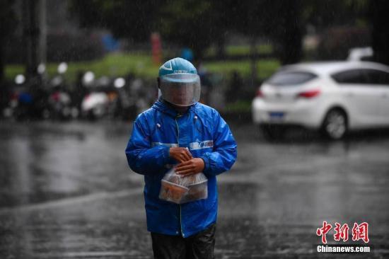 外卖小哥冒雨送餐。中新社记者 刘冉阳 摄